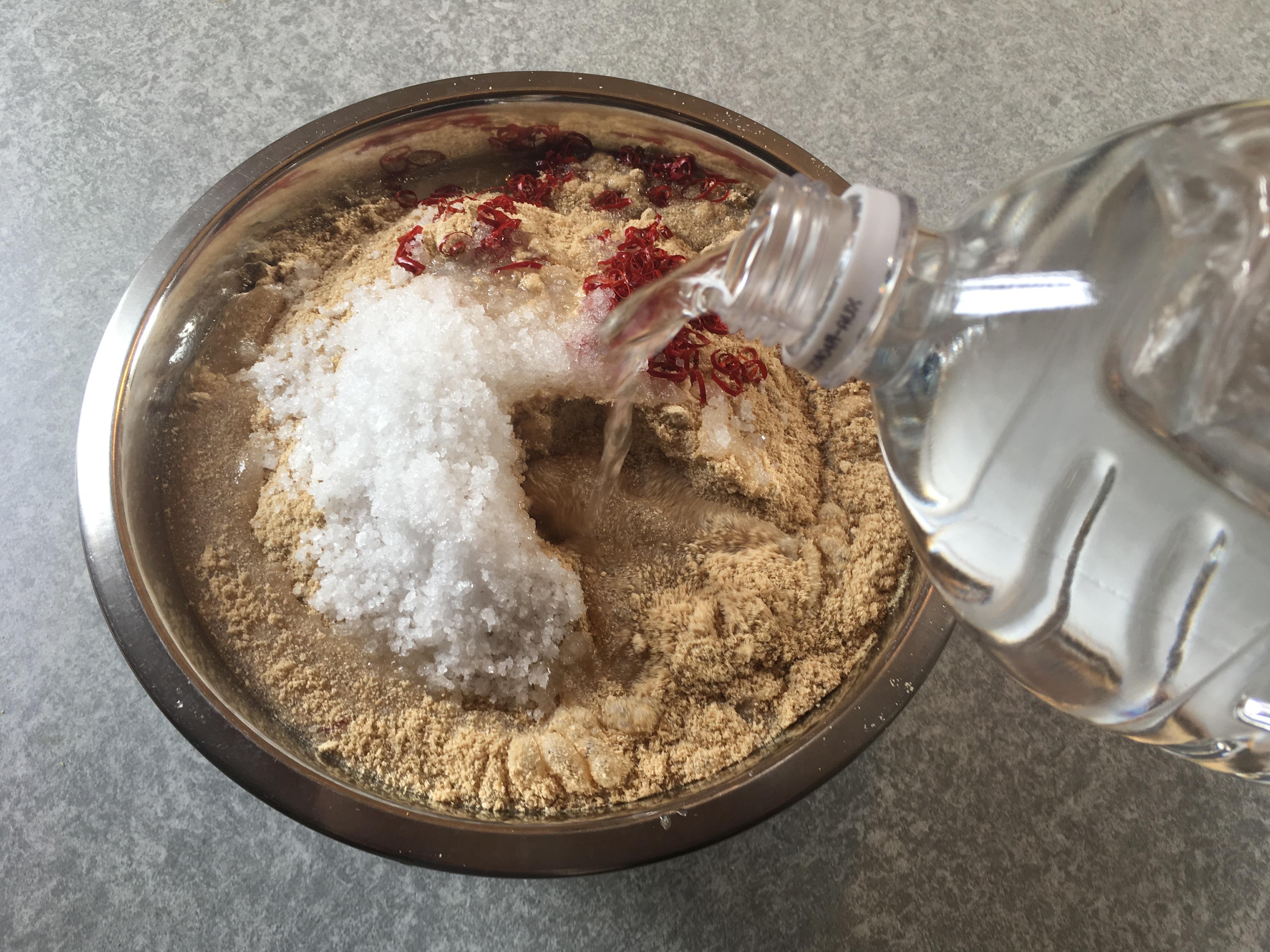 米ぬかと自然塩と唐辛子が入ったボールに水を加える